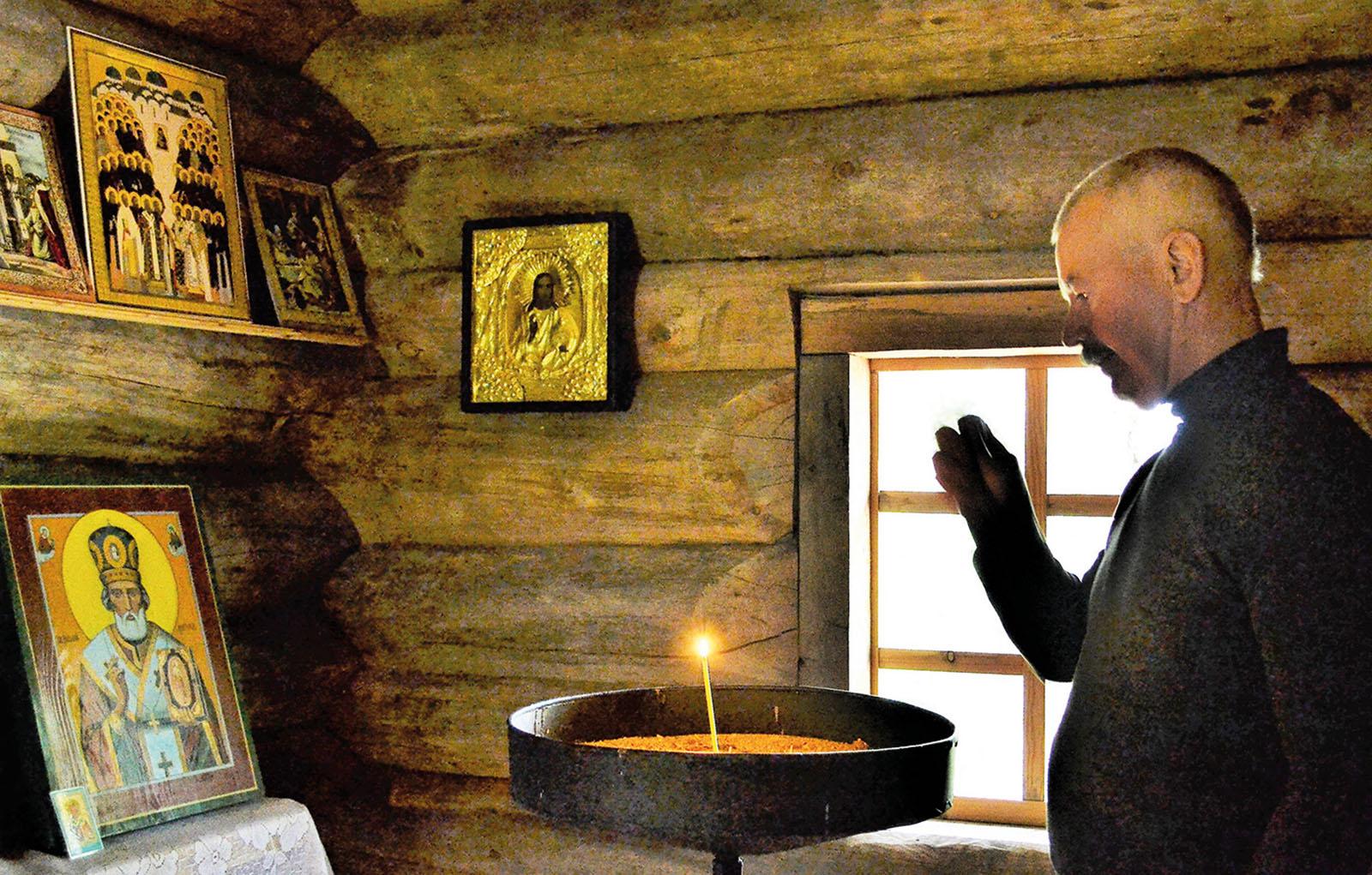 Tsasounan sisällä ikoneja hirsiseinillä, tuohus palaa Santerin edessä.