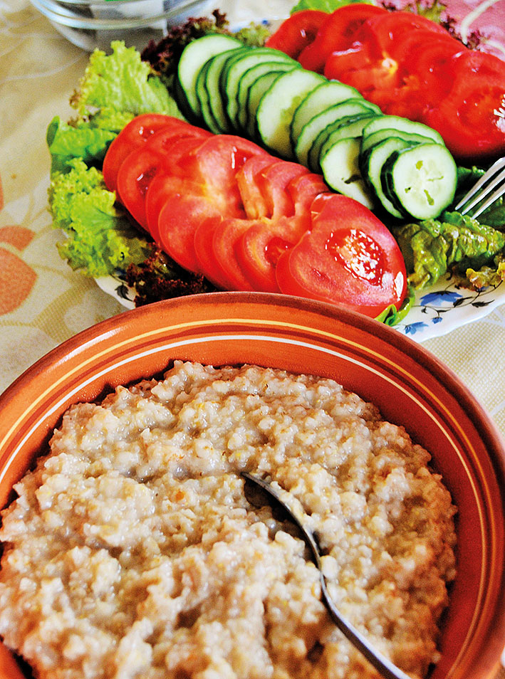Kuvassa ruokalautanen, vierellä tomaattia kurkkua toisella lautasella.