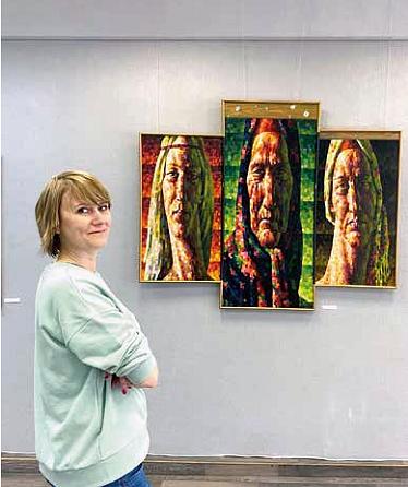 Nuori nainen seisoo taidegalleriassa kolmen eri taulun edessä.