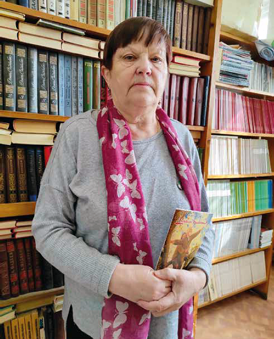 Varttunut nainen seisoo kirjastohyllyn edessä pidellen kirjaa.