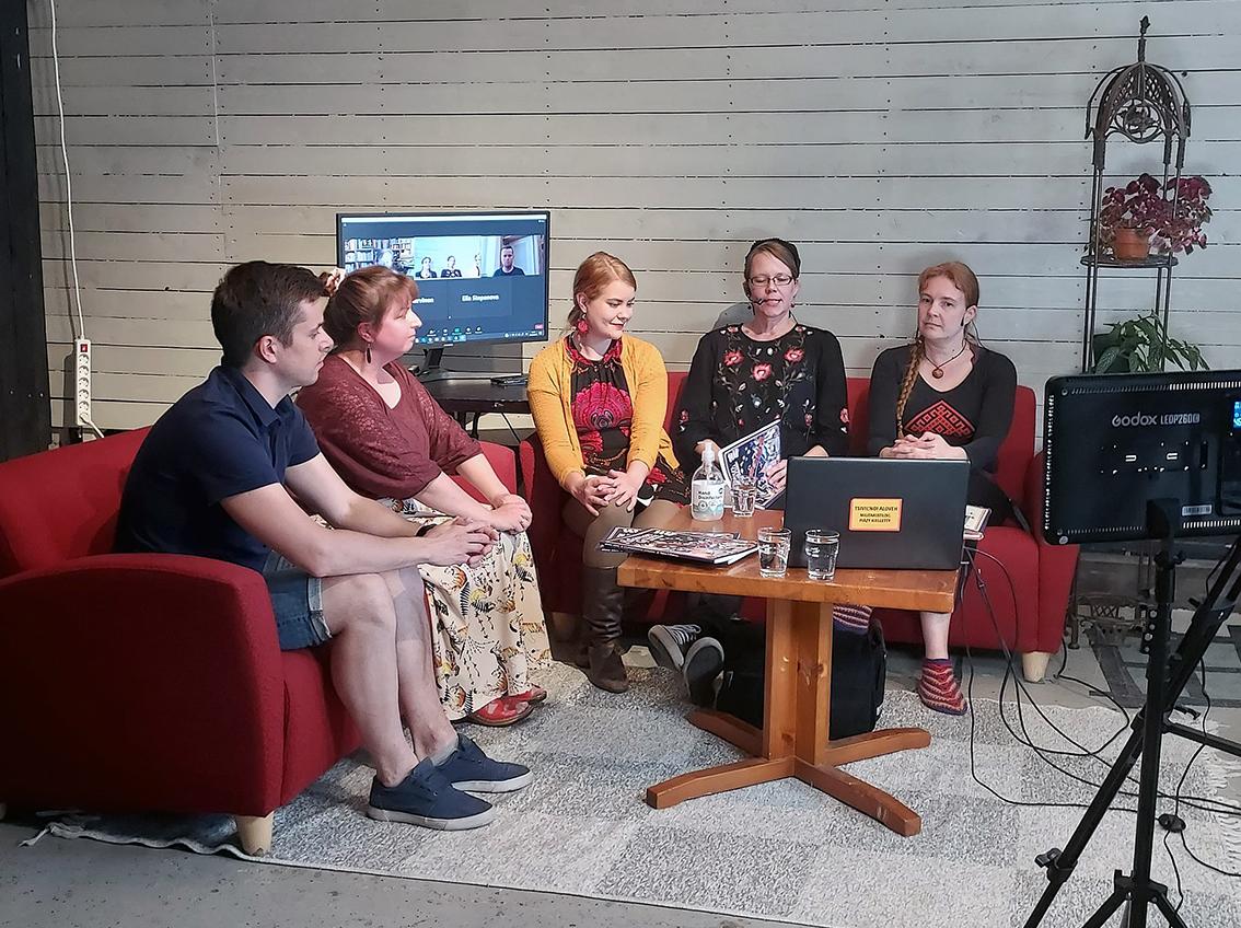 Neljä naista ja yksi mies istuvat punaisilla sohvilla, taustalla valkoinen tiiliseinä ja kamera kuvaa tätä keskustelua.