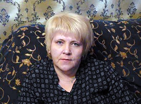 Vaaleahiuksinen nainen istuu sohvalla