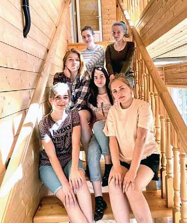 Kuusi teinityttöä istuu puisissa portaissa.