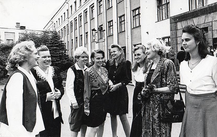 Opettaja ja seitsemän oppilasta seisovat koulun pihalla hymyillen valmistumisen kunniaksi juhla-asuissa. Kaikki ovat naisia ja taustalla on koulurakennus.