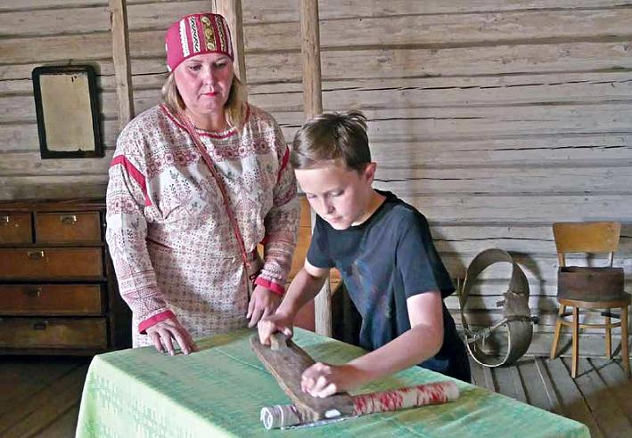 Poika silittää vanhanaikaisella silitysraudalla pöydän äärellä, kun nainen vieressä seuraa tilannetta.