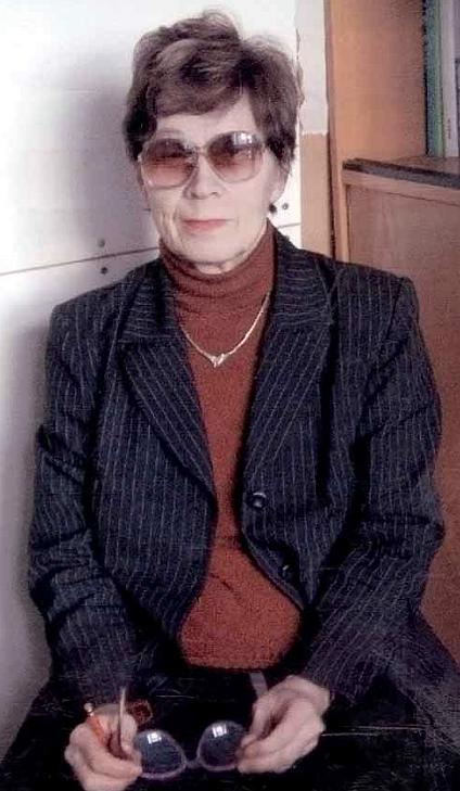 Varttunut hoikka tummahiuksinen nainen tummissa laseissa, tummassa takissa pitelee silmälaseja.