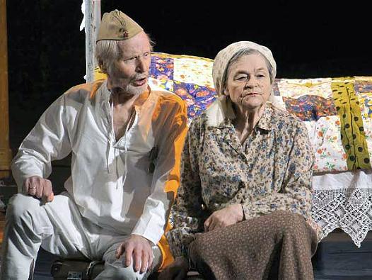 Mies ja nainen esittämässä näytelmää. Miehellä on valkoinen asu ja naisella tummahko asu.