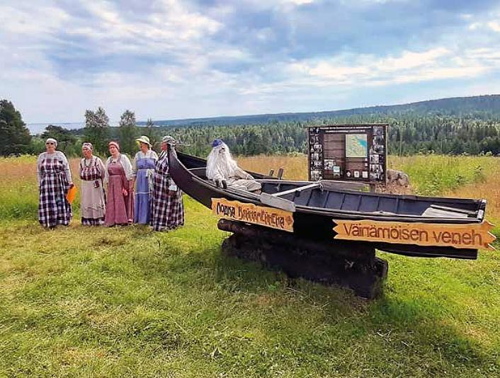 Muistomerkki, joka on vene, jossa on parrakas mies on nurmikolla. Vieressä seisoo naisia karjalaisissa kansallisasuissa ja taustalla horistontissa siintävät metsä ja taivas.