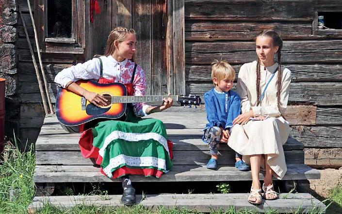 Kaksi tyttöä ja yksi poika istuvat harmaan puutalon portailla karjalaisissa perinneasuissa ja toisella tytöllä on kitara.