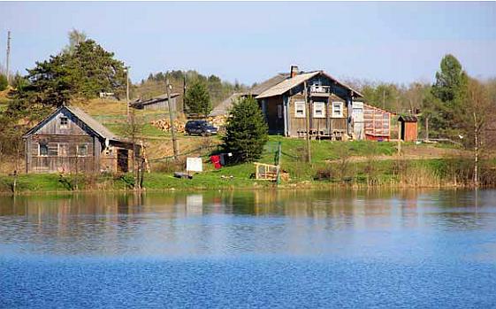 Järven rannalla kaksi puista taloa.