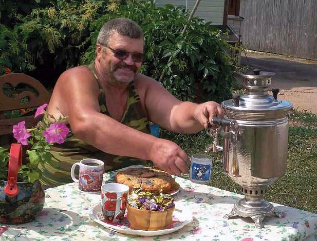 Ruskettunut hymyilevä viiksekäs mies aurinkolaseissa kaata teetä pöydän äärellä. Pöydällä on kahvileipää.i