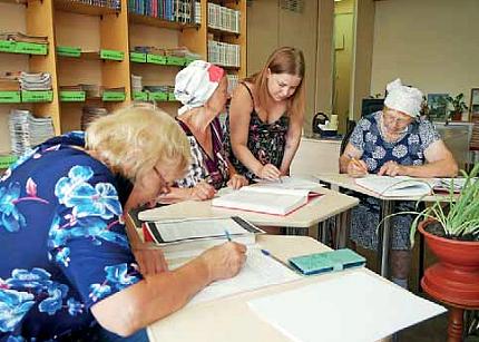 Kolme naista kirjoittaa pöydän äärellä ja neljäs nainen opastaa keskimmäistä. Pöydällä on paljon paperia.
