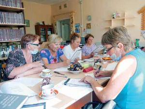 Viisi naista pöydän äärellä ja pöydällä on teekuppeja, paperia