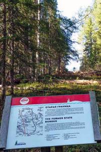 metsän keskellä olevalla aukiolla oleva kyltti merkkinä vanhasta rajasta.