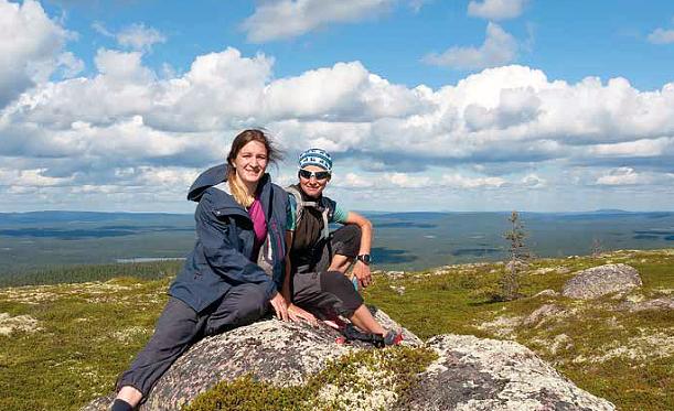 Kaksi naista vaellusvaatteissa istuvat kivellä vaaran päällä ja taustalla on sininen pilvinen taivass ja horisontti.