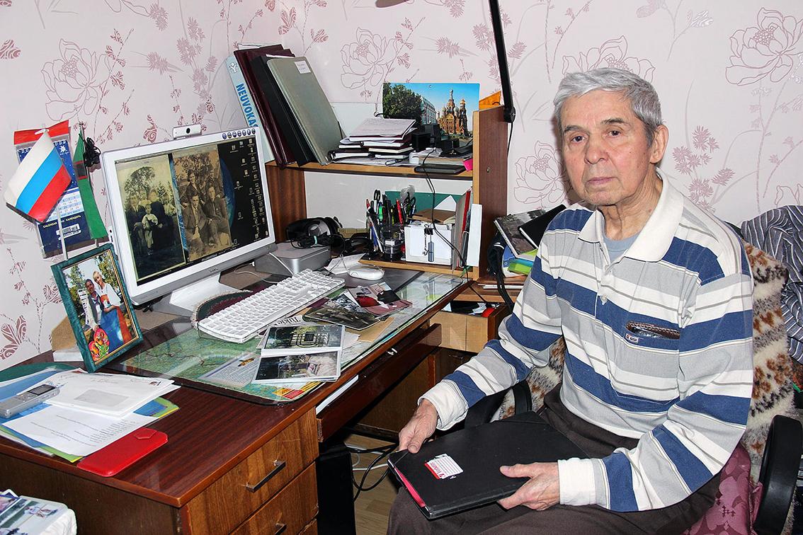 Harmaahiuksinen iäkäs mies raitapaidassa istuu pöydän äärellä missä on tietokone, paperia, kuvia liittyen tutkimukseen