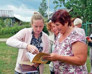 Kaksi naista tutkii kirjaa ulkona.