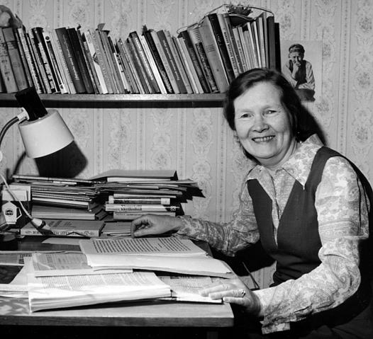 Hymyilevä nainen pöydän äärellä, jossa on paljon kirjoja ja seinällä on kirjahylly.