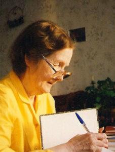 Varttunut nainen keltaisessa paidassa ja silmälaseissa kirjoittaa vihkoon