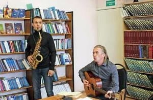 Seisova saksofonisti ja istuva kitaristi esiintyvät huoneessa, jossa on paljon kirjahyllyjä.