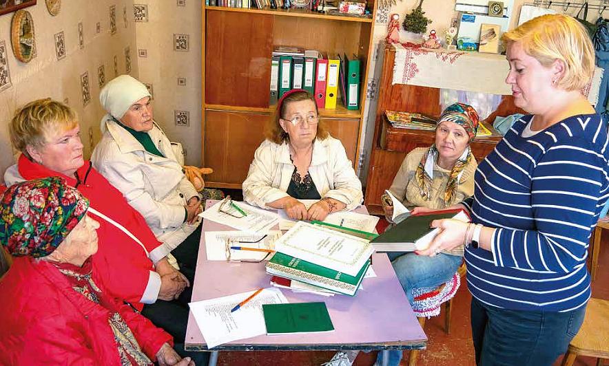Viisi naista pyödän ympärillä, joista yksi seisoo ja muut istuvat