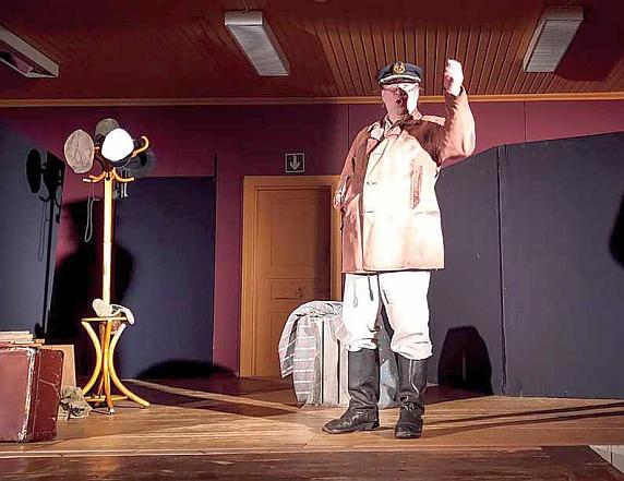 Mies pitää monologia teatterin lavalla